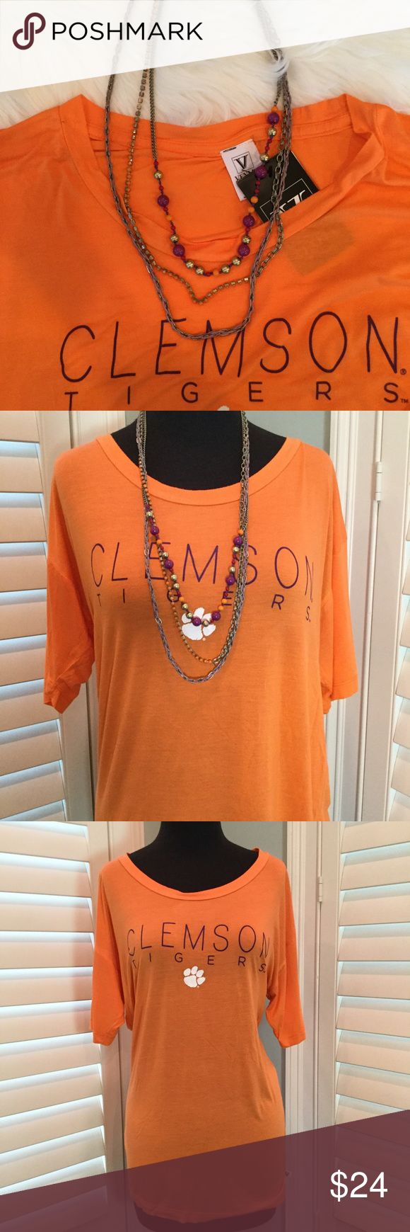 """Clemson Bundle: NWT T-shirt and Necklace, L/XL Clemson bundle of NWT women's t-shirt and preowned silver tone, orange and purple three strand necklace. Necklace is Jessica Simpson.  🔹Necklace measures 30"""" long 🔹Shirt is 92% rayon, 8% spandex  🔹Measurements laying flat: armpit to armpit 20"""", length 27"""". 🔹Condition: Shirt is new with tags attached. Necklace is in great preowned condition.  (Sandy) Tops Tees - Short Sleeve"""