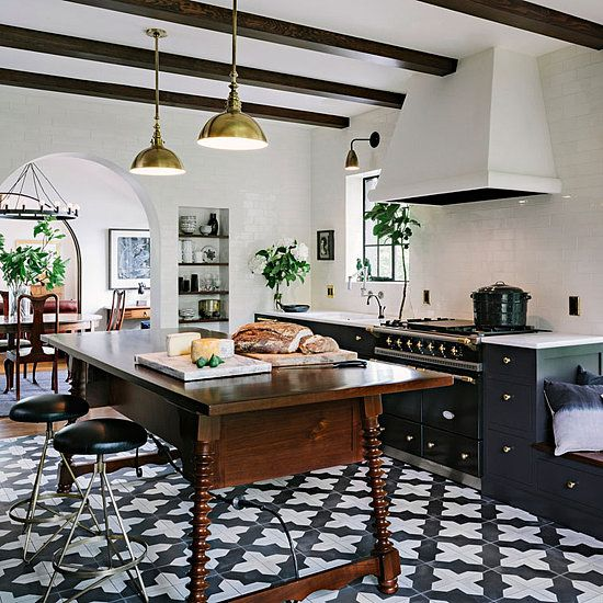 pattern tile floor kitchen, farmhouse table as island, wooden beams, black cabinets, brass pendant lights