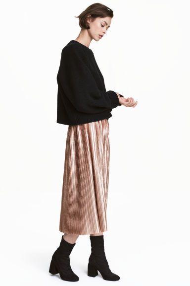 Falda plisada: Falda plisada en terciopelo arrugado con cremallera oculta en un lateral y bajo sin rematar. Largo hasta las pantorrillas.