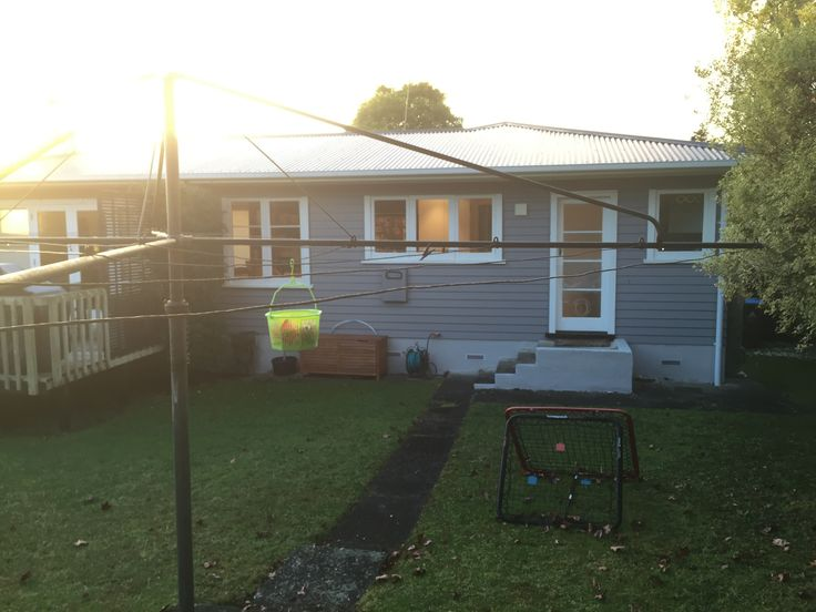 Rear of house. thin windows are over kitchen bench. Door is kitchen exit. Small window on right is laundry. Deck to left. Morning shot with sun in east.