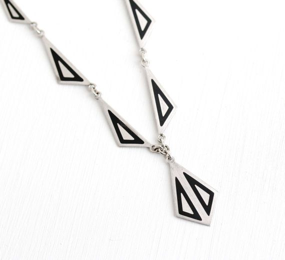 Unique vintage Art Deco Era silver tone necklace, circa 1930. This piece features linked triangular panels, detailed with black enamel. The center