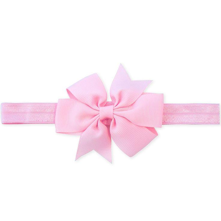 Vauvan vaaleanpunainen rusettihiuspanta.Pannan materiaali on pehmeää nylonia, joka ei paina lapsen päätä.