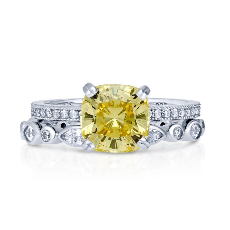"""This 2-piece solitaire ring set is the duo that every girl will say """"yes"""" to. The high setting and bold color is what makes it so outstanding. Made of rhodium plated fine 925 sterling silver. Features 2.04 carat cushion cut canary yellow cubic zirconia (8mm) in 4-prong setting. Accented with 1.03 ct.tw cubic zirconia. Bands measure 4.5mm in width."""