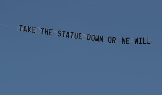 """An airplane towing a banner that reads """"Take the statue down or we will"""" flies over the Penn State campus for several hours Tuesday, July 17, 2012. The banner is presumably referring to the Joe Paterno statue outside Beaver stadium."""