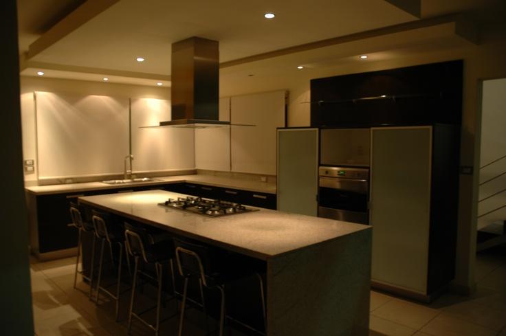 Cocina con isla cubierta de granito parrilla y campana al for Cocinas con granito