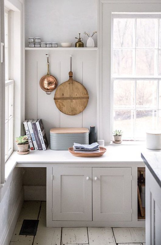 White Minimalist Kitchen With Hanging Copper Strainer And Round Wood Cutting Board Modern Bread Box