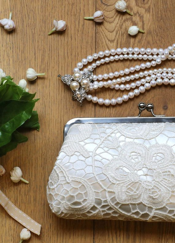 "A classic satin lace clutch in ivory is perfect for both the bride and the bridesmaids. These lace clutches are intentionally sized as travel wallets for passports and boarding passes - perfect for the destination wedding and honeymoon.  ""L'Heritage"" wedding clutch by ANGEE W."