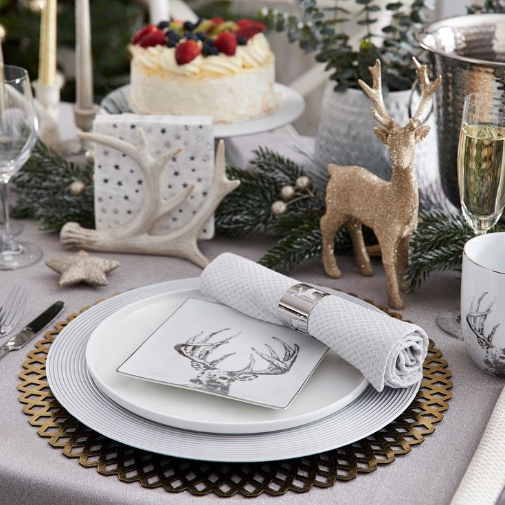 Layering your napery and crockery is a great way to instantly create an eye-catching, sophisticated style. Mix and match metallics by layering patterned round placemats complimented with gold and silver chargers and beautifully intricate reindeer plates. Little touches of elegance such as silver napkin rings paired with gold spotted napkins make all the difference in transforming your Christmas table into an elegant affair. #christmas #christmasdecorating #bedbathntable