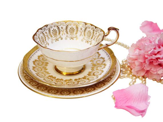 A lovely gold mismatched trio consisting of a teacup, saucer, and side plate - all having intricate gold gilding that makes each piece unique. Very stunning in person, and would make an amazing gift! Makers: Teacup: Paragon Saucer: Tuscan Side Plate: Wedgwood The teacup is in