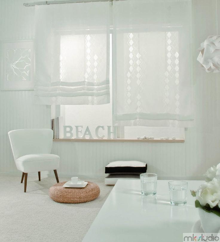 Biały salon z białymi zasłonami rzymskimi, biały fotel, styl minimalistyczny we wnętrzu - http://www.mkstudio.waw.pl/systemy-wewnetrzne/zaslony-rzymskie/