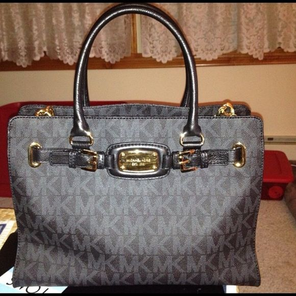 Michael Kors black handbag Black leather handbag, also has shoulder strap, with gold plate and other gold chains on side. Does have some wear and Tare on handle from being held and gold plate has a couple of minor scratches from being used but nothing crazy. The bag has a middle zipper which is a decent size plus side pockets and other zipper compartment. Michael Kors Bags Shoulder Bags