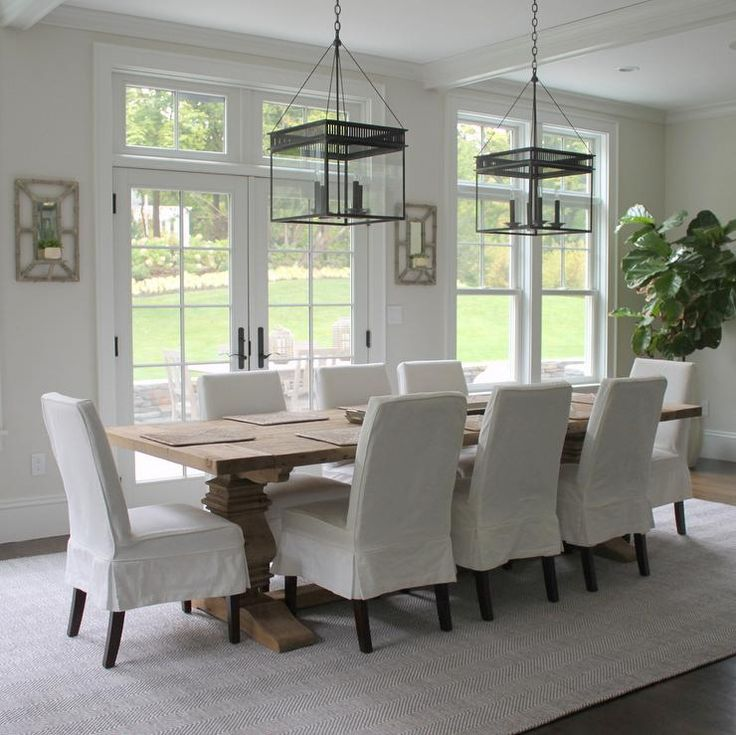 Beautiful dining room features a pair of The Urban Electric Co Chisholm lanterns illuminating a Restoration Hardware Salvaged Wood Trestle Rectangular Dining Table lined with white slipcovered skirted dining chairs placed in front of French doors leading to the backyard.
