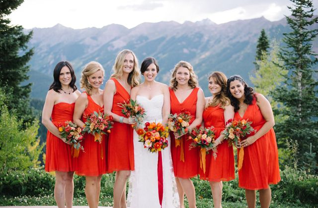 Red bridesmaid dresses pop against a green backdrop