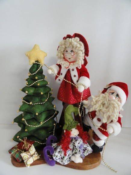 Papai e Mamãe Noel decorando a árvore de Natal. A Mamãe Noel está em cima de uma escada de madeira colocando os enfeites na árvore de Natal e o Papai Noel está lhe ajudando. Tamanho: 37 cm (altura) x 31 cm (comprimento) x 20 cm (largura) R$ 215,00