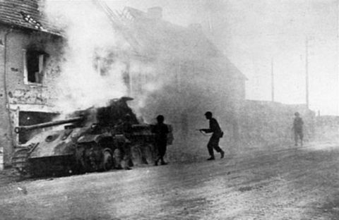"US soldiers moving near a burning German Panzer V ""Panther"" tank at Périers, France, August 1944."