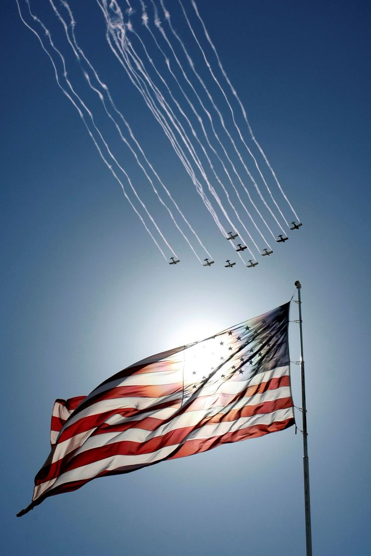 Planes fly in formation past the American flag during the national anthem before…