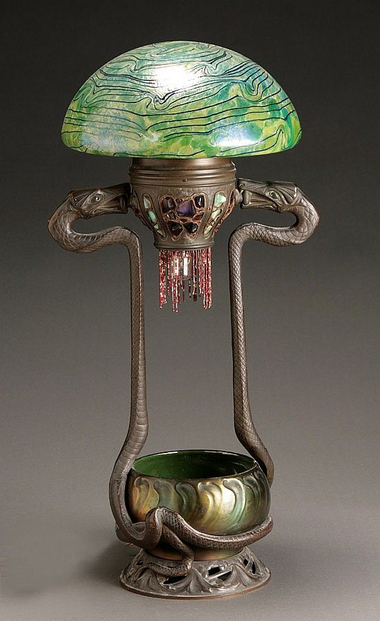 "Jewelled Bronze Serpent Table Lamp. Bronze with Inlaid Jewels, Heliosine Iridescent Glazed Pottery Bowl and a Loetz Glass Shade (Attributed). Pottery Bowl Signed ""Heliosine Ware / Austria"". Austria. Circa 1900. 28-1/4"" (71.8cm) 