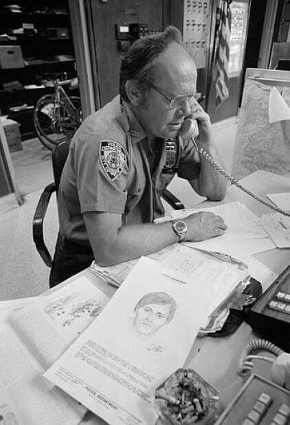 New York City police officer John Flynn takes a call at the 105th Precinct in the Flushing, Queens section of New York City, Aug. 6, 1977.