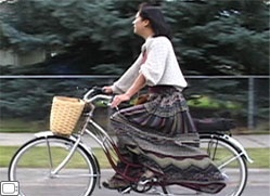 someday flowers bloom | Chiyoko Lewis rides a bicycle with a basket, her long skirt flowing in ...