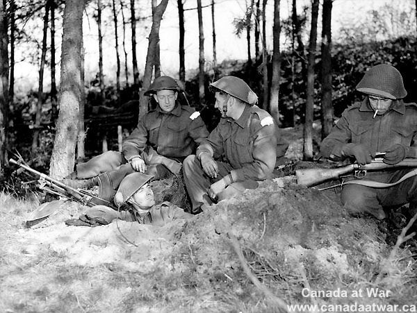 The Netherlands - Infantrymen of C Company, The Black Watch (Royal Highland Regiment) of Canada, gathered around a slit trench in the woods near Holten, Netherlands, 8 April 1945. (L-R): Privates E. Cain and Fred Cribley, Lance-Corporal Bill Curtis, Private Gord Bussey.
