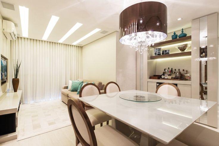 """Ao lado do espaço de jantar, foi projetada uma cristaleira que é """"cortada"""" pela estrutura que se estende do bar à parede perpendicular, formando um L. - Revista Sua Casa"""