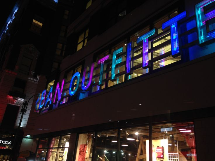 Urban outfitters front painted neon behind safety glass.