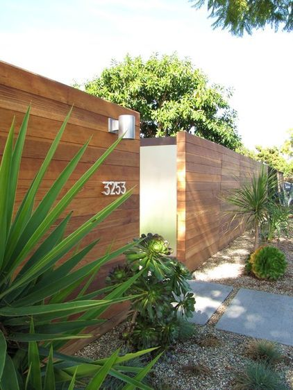 AFTER: A city ordinance allows owners in this tract to build 6-foot-tall solid fences all the way out to the curb. Enhancing Cliff May's concept of true indoor-outdoor living, the new redwood fence encloses the yard, creating a private outdoor space wrapping around the home.