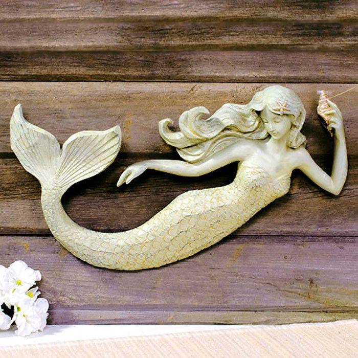 "Painted polyresin mermaid figurine carved to look like wood mounts to any flat surface. Built-in mounting. Aged finish for a completely beachy, vintage look. Sold individually. Dimensions: 10"" H x 16"""