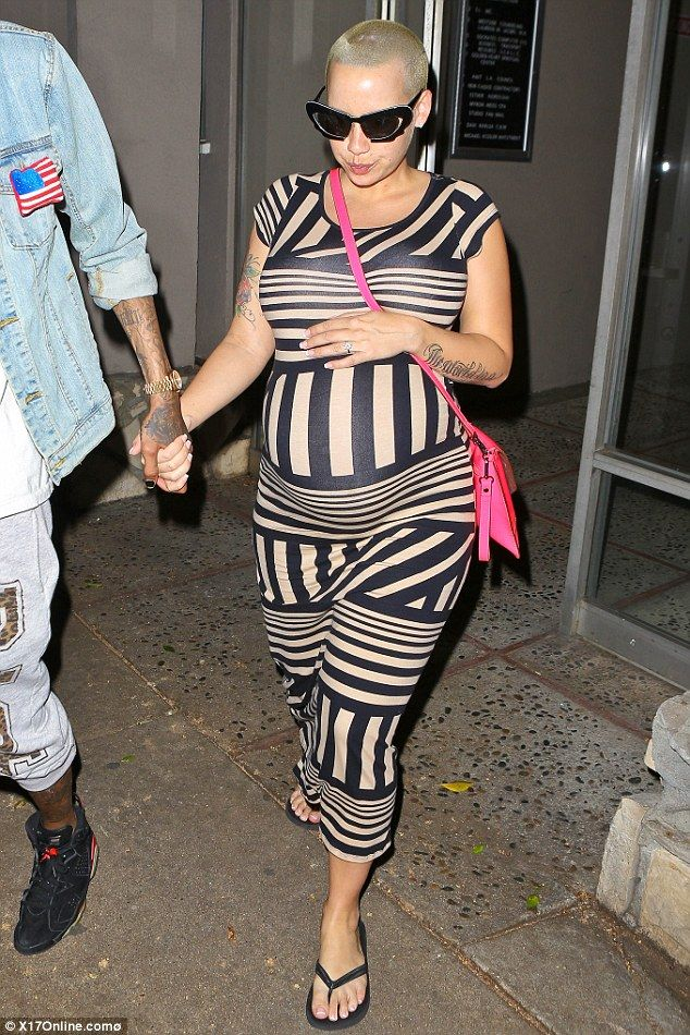 Baby on board: Pregnant Amber Rose rests a hand on her bump as she and partner Wiz Khalifa steps out in Hollywood on Sunday. I love her preggo  funky style!