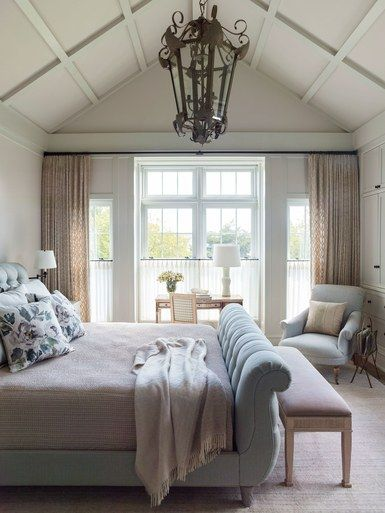 With windows on all three sides and a private balcony overlooking the garden, the master bedroom is a sunny oasis. A pale-seafoam sleigh bed anchors the space; an antique Swedish writing desk from English Country Antiques sits in front of one set of windows | archdigest.com