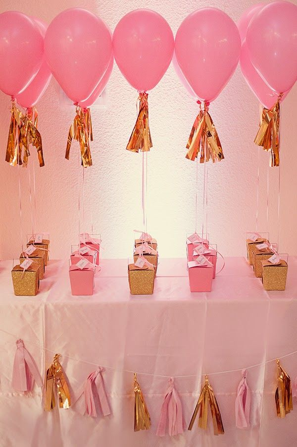 Beautiful pink and gold themed party favors act as weights to helium balloons.