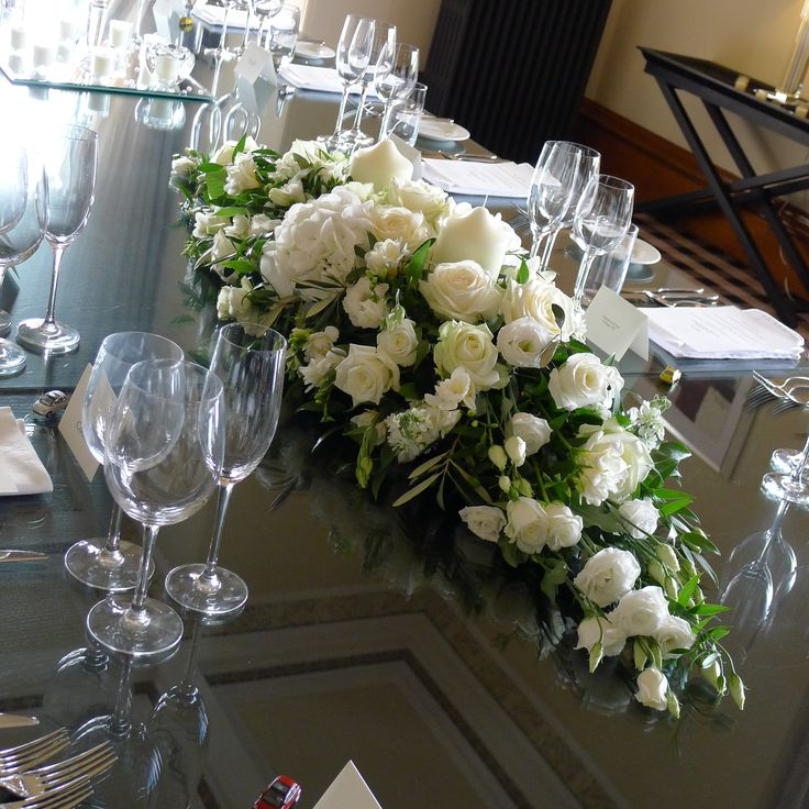 A long and low table centrepiece made up of whites, creams and green flowers.  White roses, white eustoma, white freesia and complimentary greenery were used along with cream candles in the centre to finish of the design.
