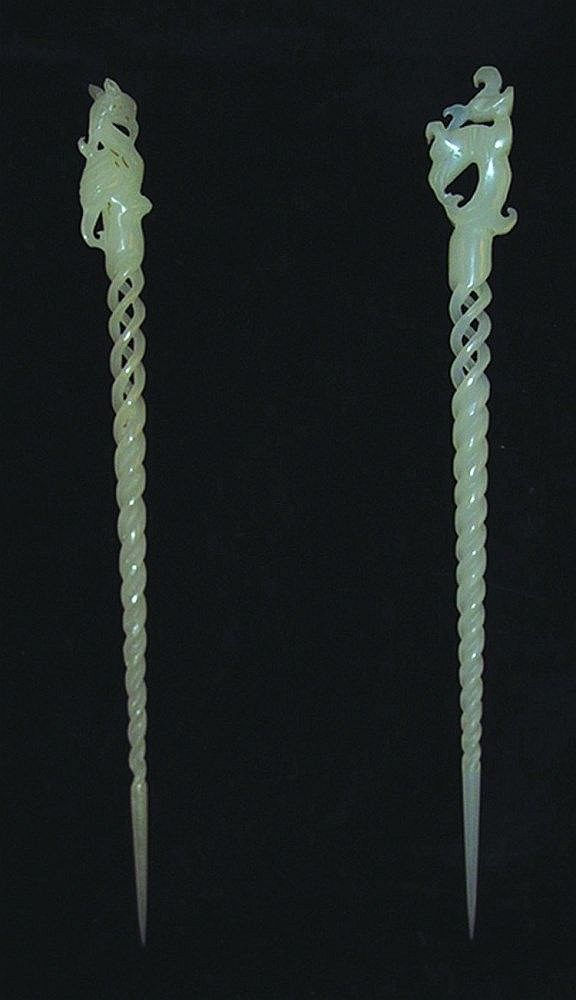 A PAIR OF CHINESE WHITE JADE HAIR PINS, each tapering spiral form partially pierced, each surmounted by a phoenix, 9.2in long
