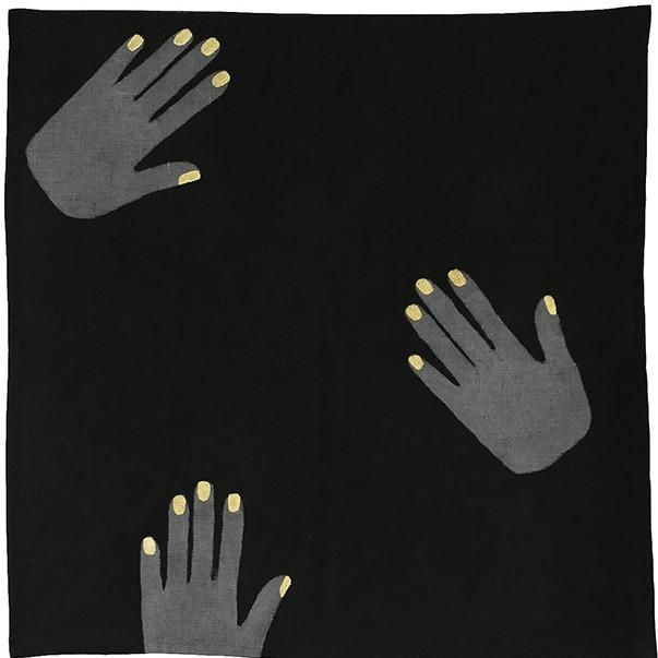black linen napkin printed with silver hands with gold nails