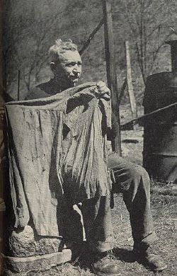 "Joe D. Hatfield holds up the shirt worn by his uncle Ellison on the day he was killed by three McCoys. There are 26 knife holes in it. The three McCoys were killed the same day; one of them, Little Randall, 15, was told to beg for his life but replied, ""Go to hell,"" and was shot."