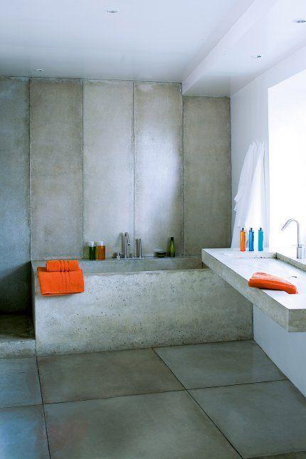 Une salle de bains entièrement bétonnée  Aménagée dans un style minimaliste comme dans la cuisine, la salle de bains est habillée de plaques de béton coulé des murs au sol. La robinetterie contemporaine de chez Boffi s'accorde avec les matériaux bruts. Les serviettes du BHV et les produits de beauté Shu Uemura apportent une touche de couleur, toujours dans les tons orangés pour conserver une harmonie dans l'appartement.