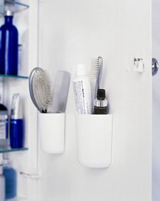 Mount flat-backed self-adhesive cups on the inside of the medicine cabinet door to hold combs, brushes, and toothpaste more efficiently.