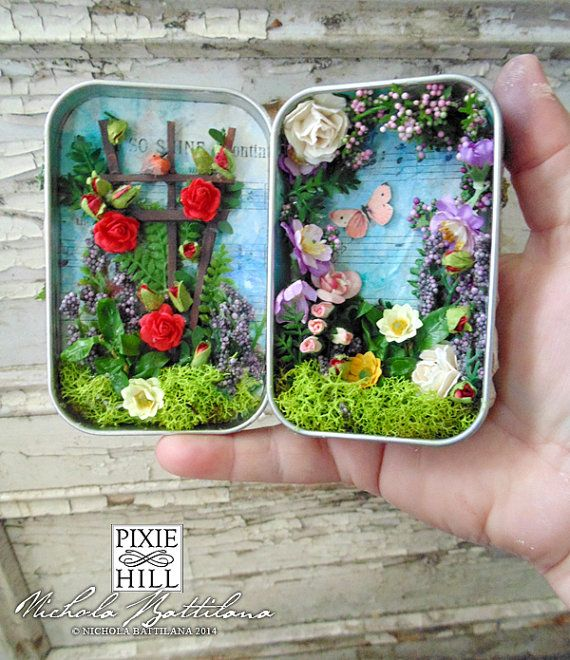 Ive created a tiny secret garden inside an Altoids style tin. The design is inspired by the classic book The Secret Garden by Frances Hodgson Burnett.  The tin measures approximately 2.4 x 3.75 x 1 (give or take a hair). The exterior features handmade stone work, ivy and plants, and an arched wooden door with tiny keyhole. I often recycle materials in my work and the paper on the interior of the tin is from a discarded vintage hymn book. Some of the text is visible through the paint. Inside…