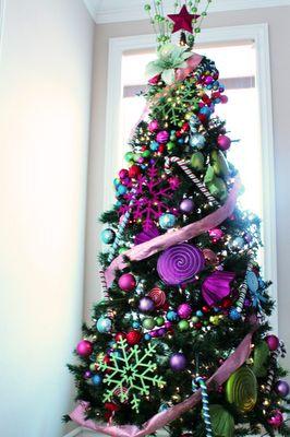 Árbol con adornos de caramelos gigantes y colores. Es precioso, tipo Rompe Ralph.