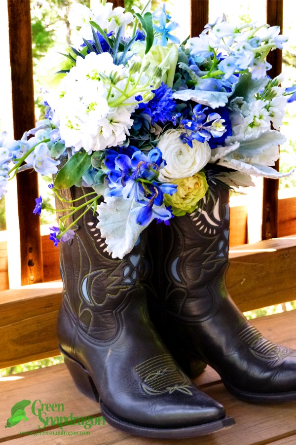 Blue bridal bouquet in a boot for a Texas Hill Country wedding. Bouquet includes green beauty roses, green tea roses, hydrangea, stock, delphinium, dusty miller, ranunculus, sea thistle, tweedia, cineraria, cornflowers, blue-dyed roses, texas bluebonnets.