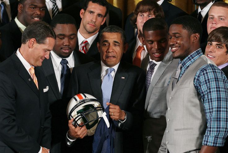 President Barack Obama (C) holds an Auburn Tigers helmet given to him by members of the 2011 BCS National Champion Auburn University football team including Cameron 'Cam' Newton (2nd-R), Kodi Burns (R), and Auburn head coach Gene Chizik (L) in the East Room at the White House, on June 8, 2011 in Washington, DC. The Auburn Tigers defeated the Oregon Ducks in the 2011 BCS National Championship Game on January 10. (Photo by Mark Wilson/Getty Images)                          ...