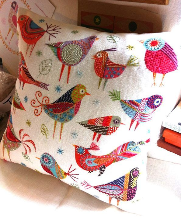 Colorful embroidered folk art birds on a pillow,