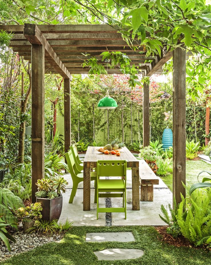 A pergola creates an outdoor room in the backyard, complete with a dining table, an outdoor pendant light, and shade provided by a nearby sycamore tree.