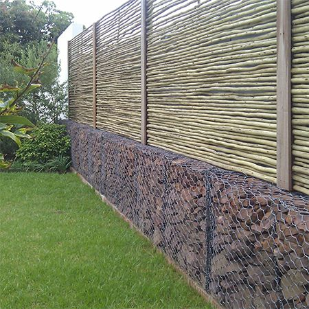 To bring down the cost of installing a gabion wall, consider using gabions only for the lower section and installing bamboo or pole fencing for privacy at the top.