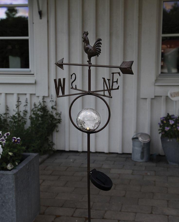 Pynt opp hagen med denne staute vindhanen fra Star Trading. Vindhanen har en liten dekorativ kule i midten som lyser opp når skumringen kommer og vil tilføre den en ekstra koselig detalj.