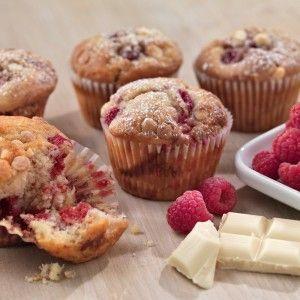 Muffins with raspberries and white chocolate with raspberries on the side and white chocolate pieces.