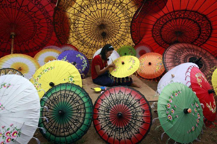 A girl paints on an umbrella in Pathein township, Ayeyarwady Delta, Myanmar