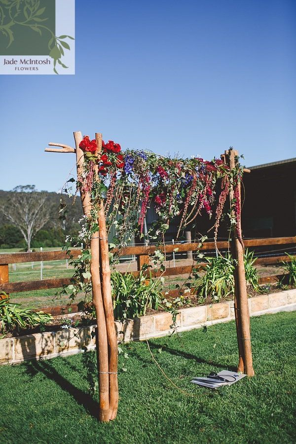 A perfect spring day for an outdoor wedding. We decorated our two-post arbour with burgundy amaranths, ivy, purple hyacinth and bright red roses. www.jademcintoshflowers.com.au www.littleblackbowphotography.com.au