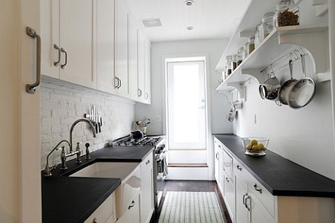 Lovely skinny galley kitchen - beautiful dark counter tops, simple hefty cabinet handles on white doors; apron sink, extra open shelving.