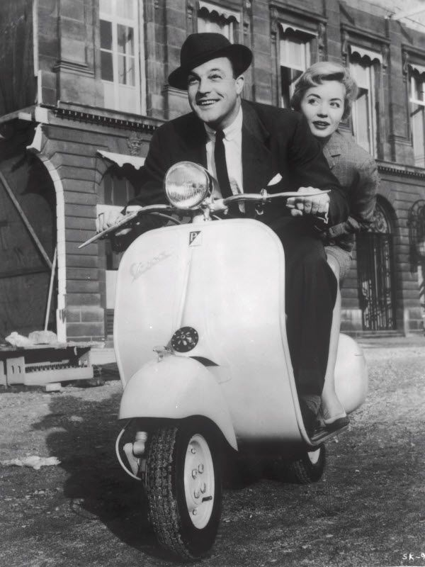 Gene Kelly riding a scooter